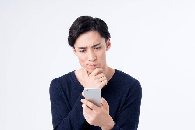 スマートフォンを片手に悩む男性