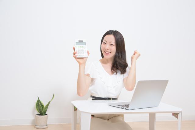 ノートパソコンの前で電卓を片手に喜ぶ女性
