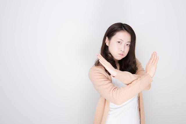 バツ印を出す女性
