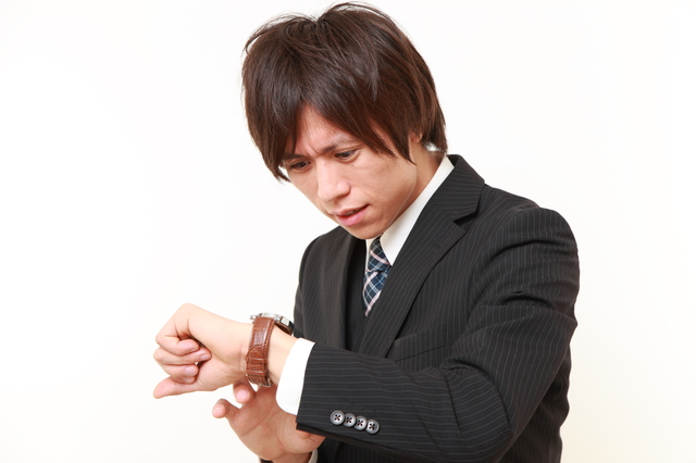 腕時計を見て焦っている男性