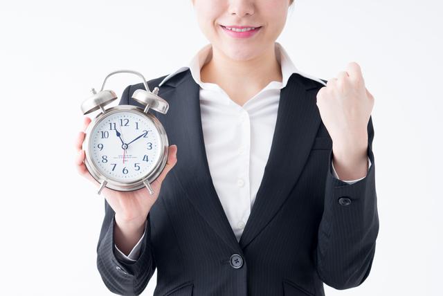 時計を持ってガッツポーズする女性