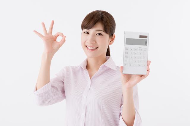 電卓を持って喜ぶ女性